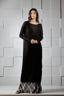 Garota atraente na camisola de lã longa malha e saia