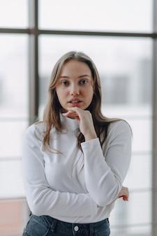 Garota atraente na janela mostra diferentes emoções e humor.