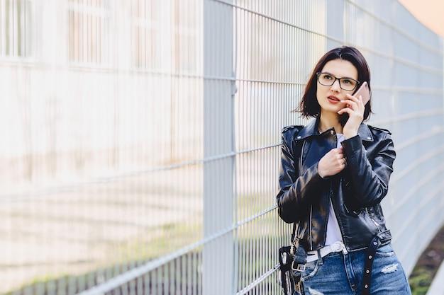 Garota atraente na jaqueta de couro em copos falando no telefone