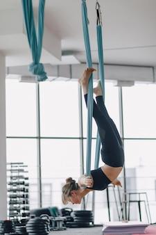 Garota atraente no ginásio durante yoga e yoga fly, posando e com boa aparência