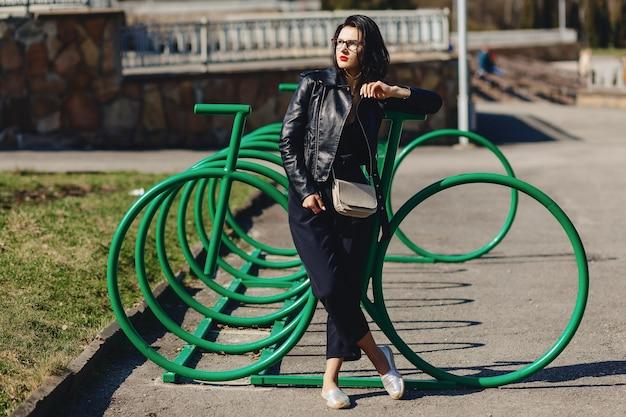 Garota atraente no parque ensolarado perto de estacionamento de ciclo