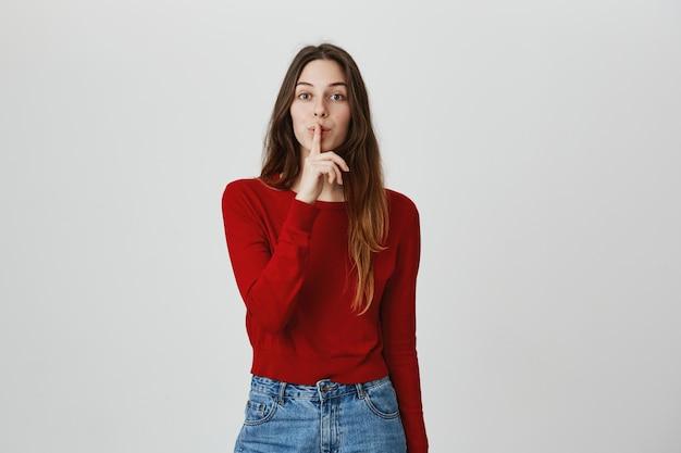 Garota atraente pedindo silêncio, silêncio com o dedo sobre os lábios, tem segredo