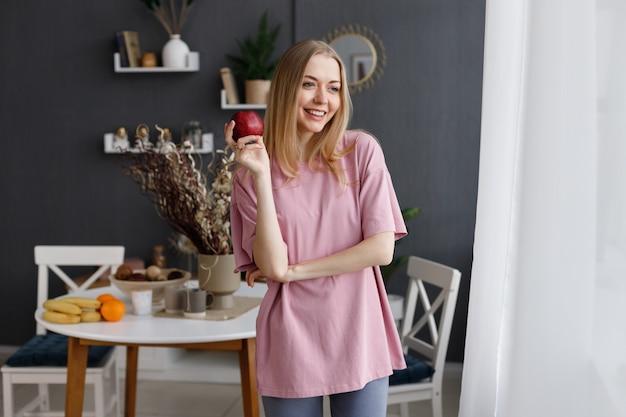 Garota atraente perto da mesa com uma maçã sorrindo