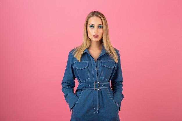 Garota atraente posando em fundo rosa em uma tendência geral da moda de jeans