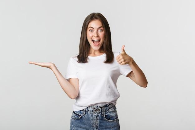 Garota atraente satisfeita segurando algo por lado e mostrando o polegar para cima em aprovação.