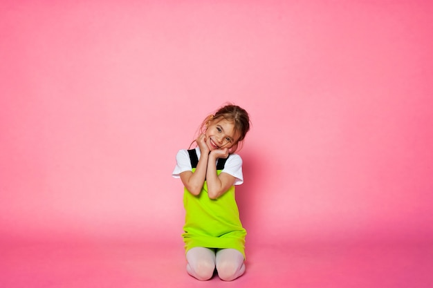 Garota atraente se divertindo no fundo rosa