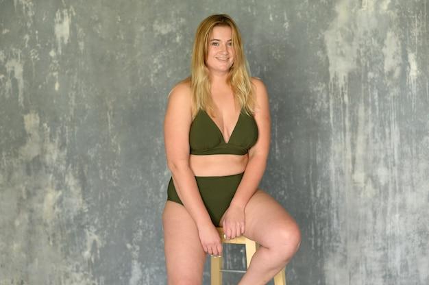 Garota atraente sentada em uma cadeira de cueca.