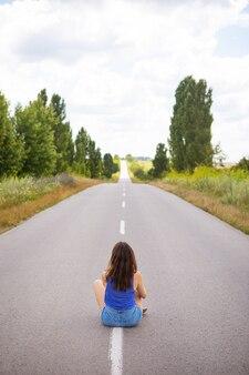 Garota atraente sentada no asfalto e posando no meio da estrada de asfalto perto do campo