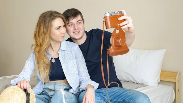 Garota atraente, sentado na cama, fazendo selfie com uma câmera velha, experimentar chapéu-coco posando e sorrindo no quarto