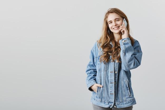 Garota atraente sorridente falando no telefone com uma cara feliz