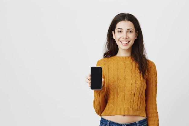 Garota atraente sorridente mostrando o aplicativo, apontando o dedo na tela do celular
