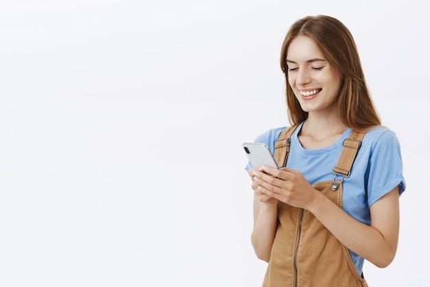 Garota atraente sorridente usando telefone celular, mensagens de texto ou navegando em redes sociais