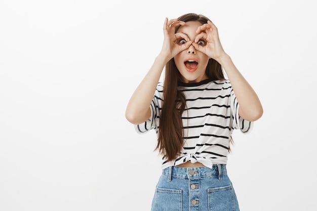 Garota atraente surpresa e maravilhada olhando pelo binóculo de dedo, avistando algo incrível de longe