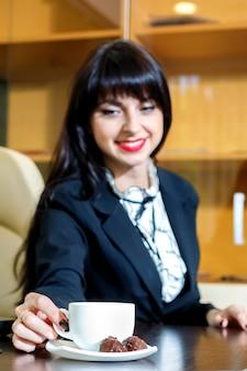 Garota atraente toma uma xícara de café em uma mesa no escritório
