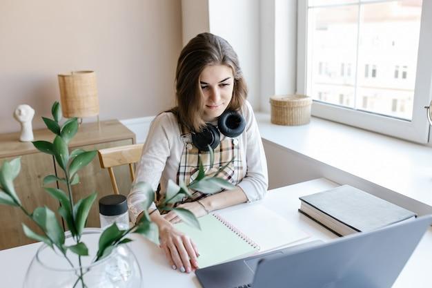 Garota atraente usando fones de ouvido estudo com professor de skype de bate-papo na internet se preparando para o exame