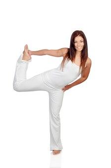 Garota atraente vestida de branco praticando ioga