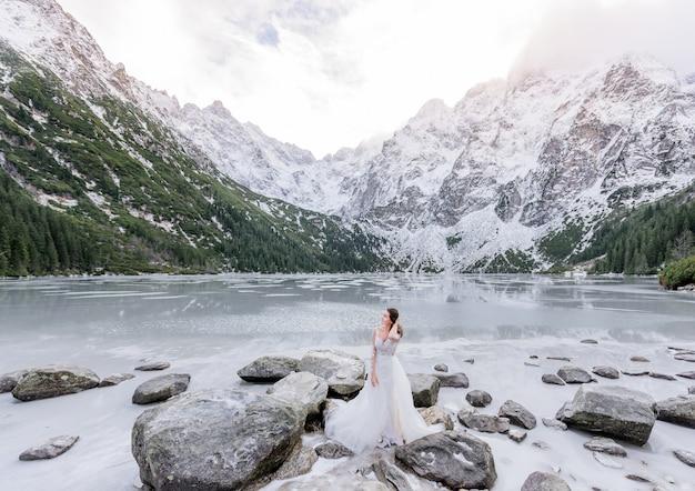 Garota atraente vestido branco está de pé na frente do lago congelado, rodeado por montanhas nevadas