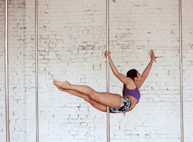 Garota atravessa as pernas dela enquanto ela executa pole dance no estúdio