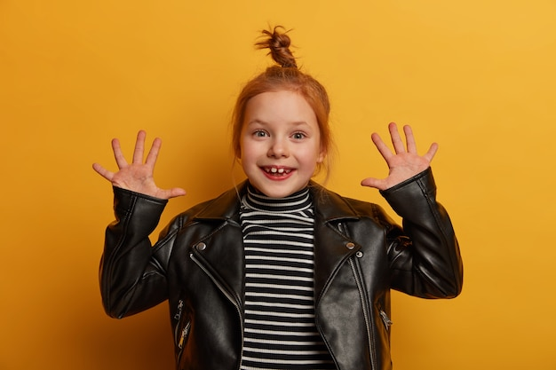 Garota bastante otimista com cabelo rapado levanta as palmas das mãos, tem expressão alegre, vestida de suéter listrado e jaqueta de couro, estando de bom humor, espera pelos pais, isolada sobre parede amarela
