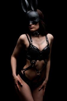 Garota bdsm em uma linda lingerie sexy de couro preto e máscara