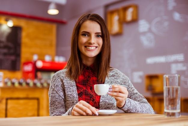 Garota bebe café e poses