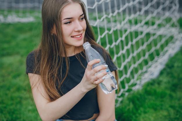 Garota bebe uma água