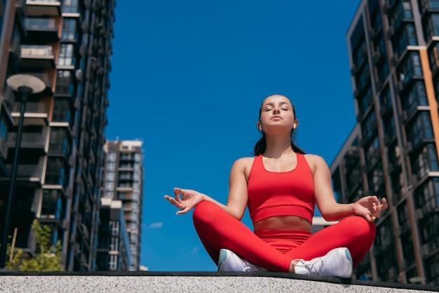 Garota bem construída e flexível relaxando em pose de ioga de lótus