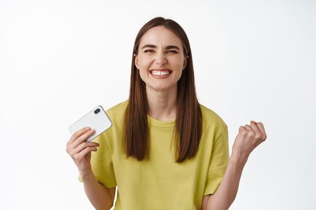 Garota bem sucedida parece satisfeita, segura o smartphone e a bomba de punho, sorrindo satisfeito, comemorando a vitória, ganhando no telefone, parado em branco.