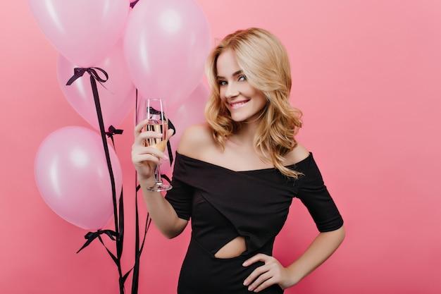 Garota bem vestida com um copo de vinho comemorando seu aniversário com um sorriso encantador. foto interna de mulher loira elegante com monte de balões na parede rosa.