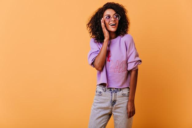 Garota bem vestida olhando em volta com um sorriso. mulher africana encaracolada romântica sorrindo em laranja.