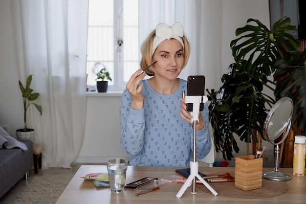 Garota blogueira conta aos assinantes sobre cuidados com a pele e maquiagem. conceito de blog, transmissão e cosméticos