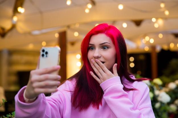Garota blogueira e influente ruiva surpresa falando fazendo videochamada usando smartphone com seus assinantes nas redes sociais.