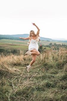 Garota boho muito jovem em uma colina com campo de verão