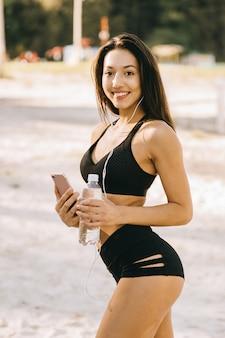 Garota bonita aptidão com longos cabelos escuros, vestindo um top preto e shorts, ouvindo música com fones de ouvido no parque verde