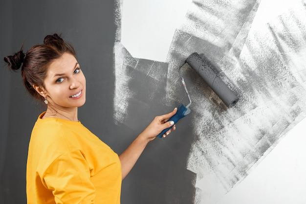 Garota bonita camisola amarela pinta uma parede em tinta cinza. sala de pintura, reparação, design. copie o espaço.