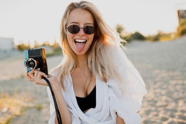 Garota bonita com câmera retro, fazendo caretas e posando na praia perto do oceano. férias de verão. linda luz do sol.