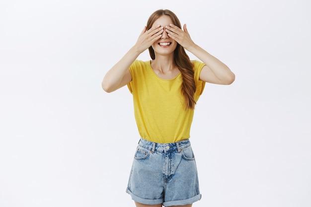 Garota bonita despreocupada cobrindo os olhos com as mãos e sorrindo, esperando a surpresa