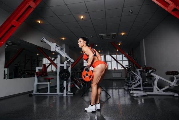 Garota bonita e atlética treina e faz fitness no ginásio.