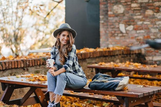 Garota bonita em calças jeans curtas sentada em uma mesa de madeira no parque outono