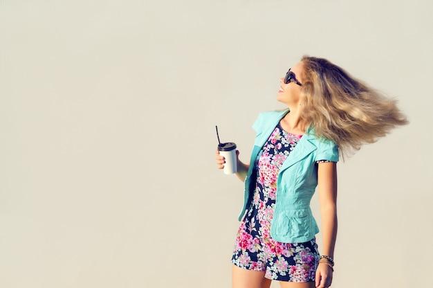 Garota bonita em roupas da moda, copo na mão