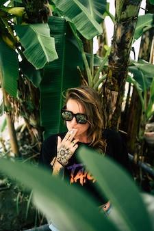 Garota bonita em shorts jeans com pernas longas, posando em localização tropical perto de palmeiras