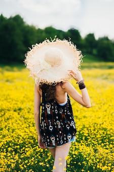 Garota bonita em um campo de flores amarelas
