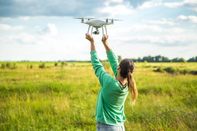Garota bonita em um campo lança o drone no céu