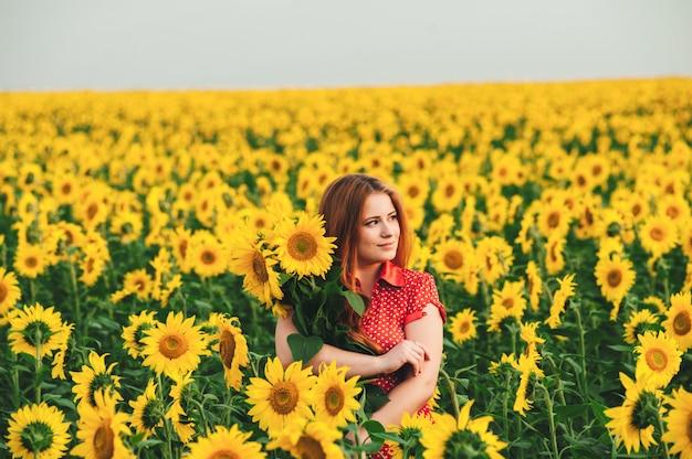 Garota bonita em um enorme campo amarelo de girassóis.