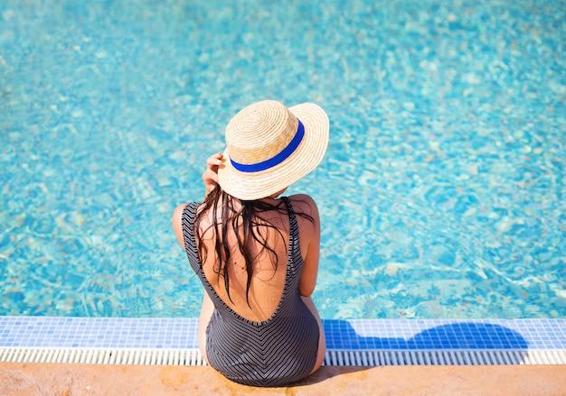 Garota bonita em um maiô preto perto de uma piscina azul.