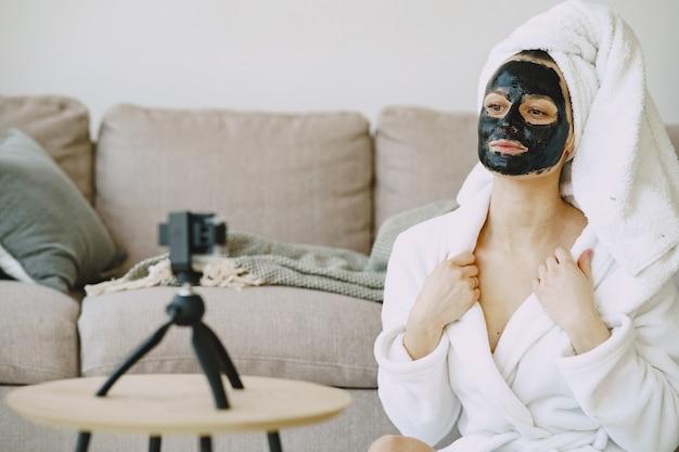Garota bonita em um roupão de banho branco em casa gravando um vídeo