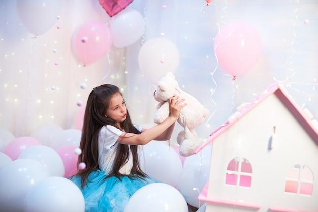 Garota bonita em um tutu colorido saia exuberante no cenário dos balões segurando no brinquedo de pelúcia rocas. balões de papel alumínio e látex cheios de hélio.