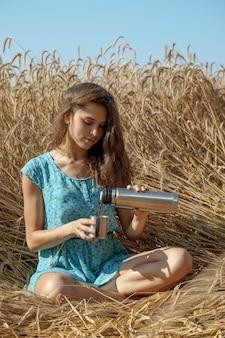 Garota bonita em um vestido azul senta-se no campo de trigo e bebe chá ou café de garrafa térmica