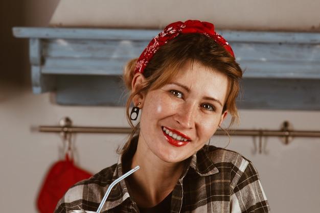 Garota bonita em uma bandana bebe coca-cola através de um canudo, sorrisos, lábios vermelhos, senta-se em casa na cozinha. publicidade, ano novo conceito. foto pin-up.