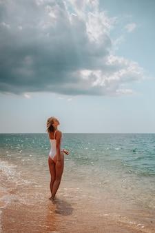 Garota bonita em uma roupa branca caminha ao longo da costa do mar azul